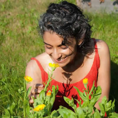 Head and shoulder photo of Dr. Priya, smelling yellow flowers